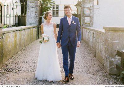 Tim in een blauw trouwpak met peachkleurige das